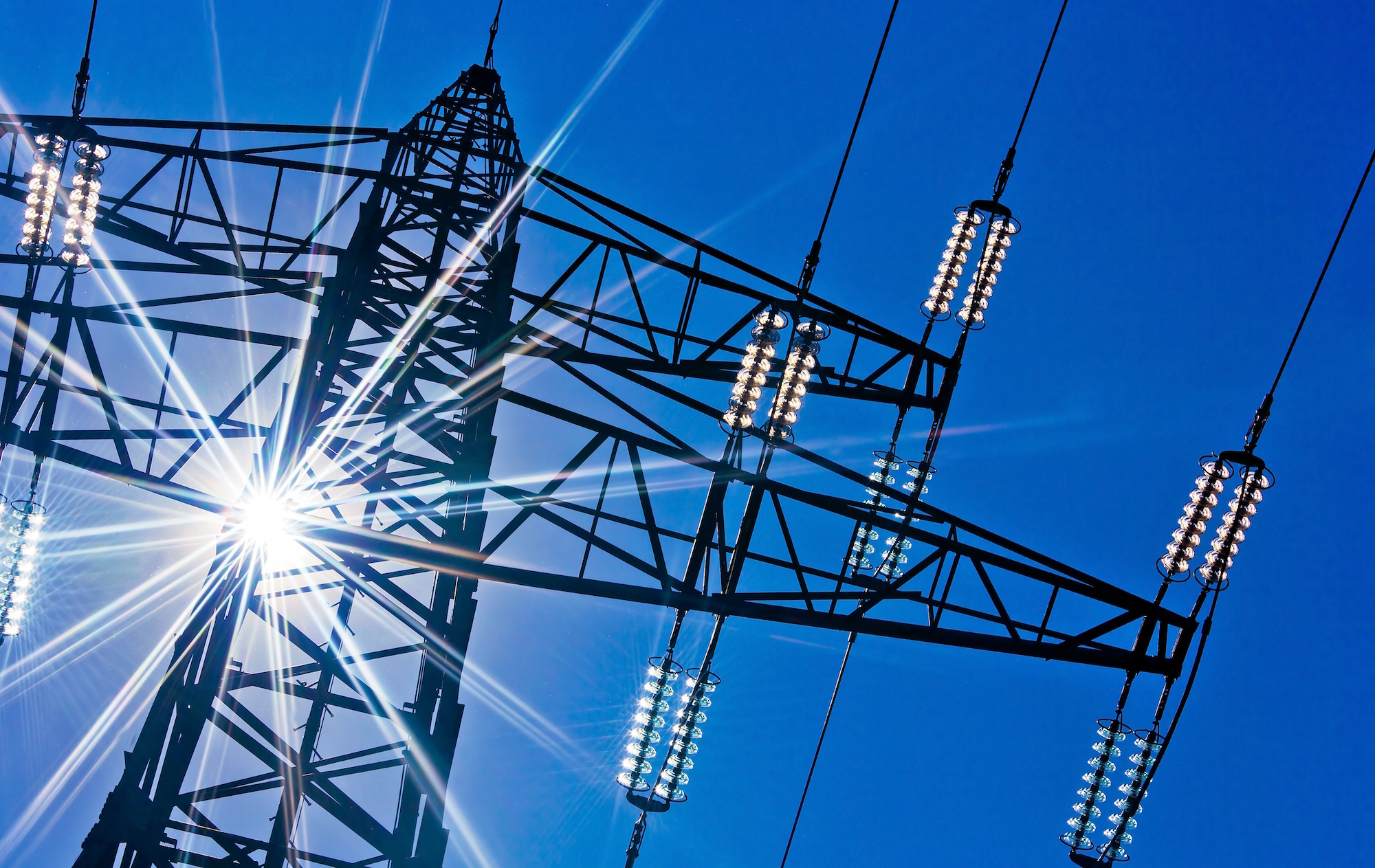 14359476 - a high-voltage electricity pylons against blue sky and sun rays